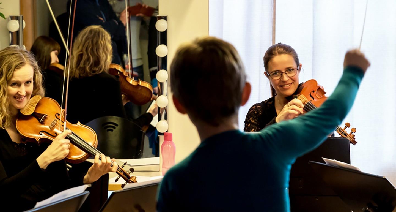 Gutt dirigerer to orkestermusikere